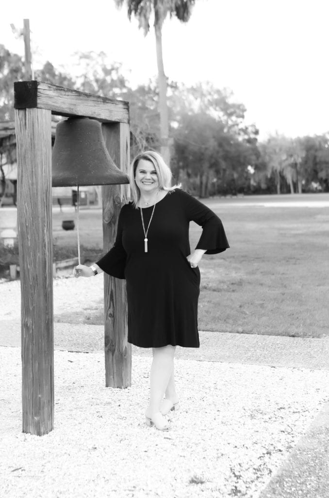 LIFE COACH LISA MARIE RUNFOLA STANDING BY A BELL AT THE PARK